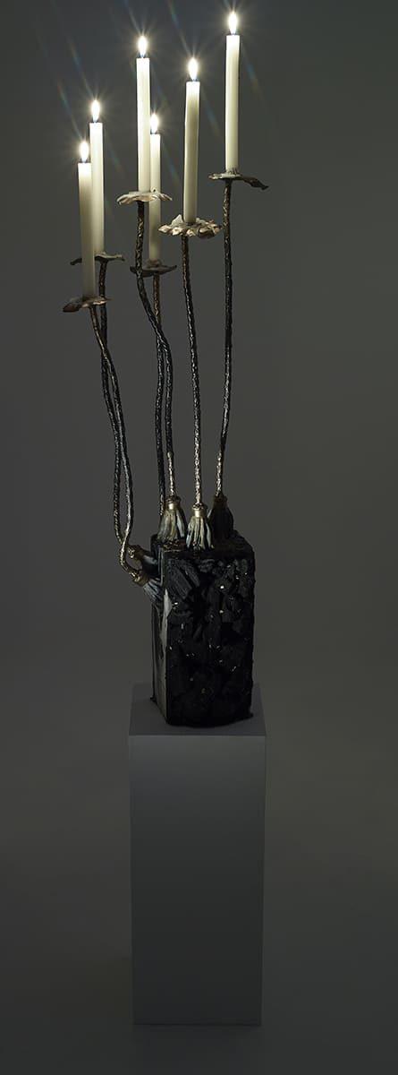 Présentation de nuit et bougies allumées, de la sculpture fonctionnelle Carbon Rock Pad