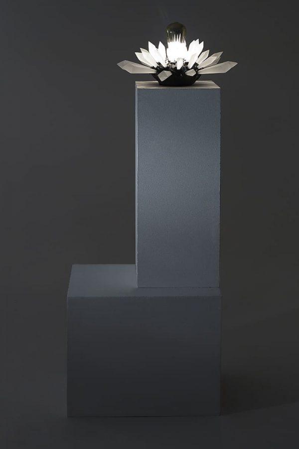 Présentation de l'oeuvre lumineuse Carbon Rock Wall Light allumée et dans le noir.
