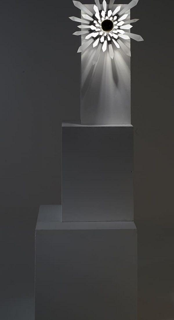 Présentation de face et entière de la sculpture lumineuse Carbon Rock Wall Light, allumée et dans le noir